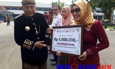 Bupati Malang Drs HM Sanusi saat memberikan penghargaan kepada Aini, guru kreatif dan produktif dari SDN 2 Girimoyo. (gie)