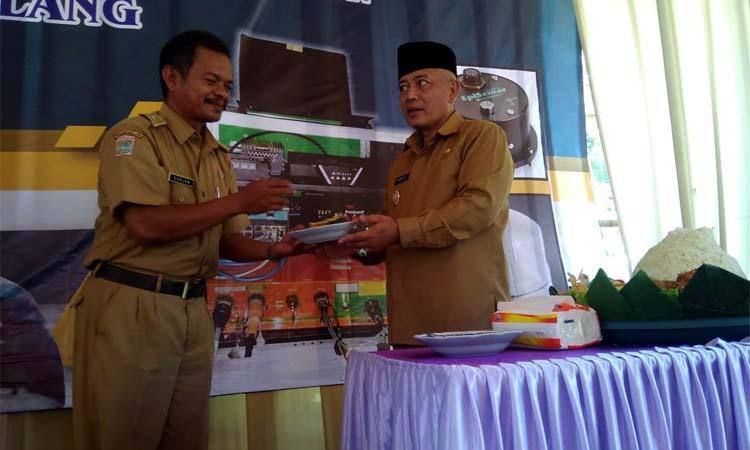 Bupati Malang Drs HM Sanusi MM Serahkan Potongan Tumpeng Kepada Soelan Kades Sidodadi. (Sur)